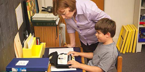 Boy learning braille on an assistive device.