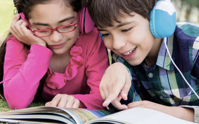 Two children looking at a book and listening to the text through headphones.