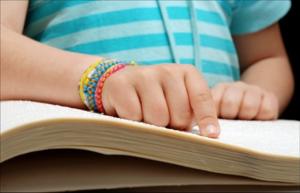 Elementary child reading braille.
