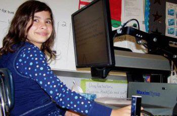 Young girl sitting at an CCTV monitor.
